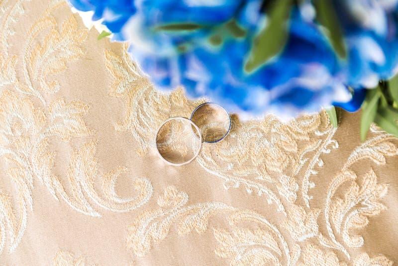 结婚戒指在织品说谎在一束花旁边 免版税库存照片