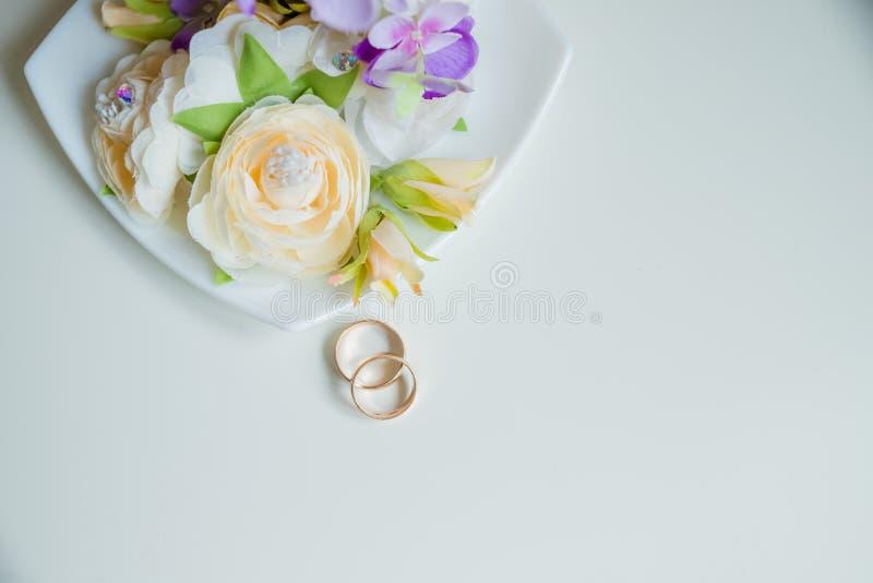 结婚戒指,美丽的花束,新娘辅助部件 婚姻的请帖 有花和全部的金结婚戒指  库存图片