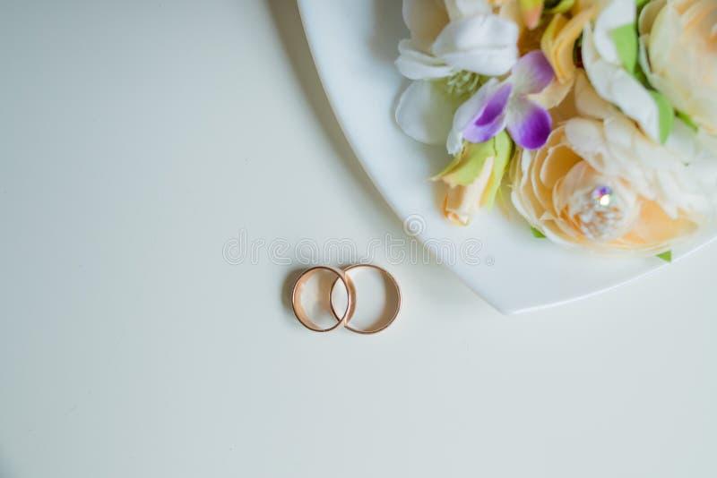 结婚戒指,美丽的花束,新娘辅助部件 婚姻的请帖 有花和全部的金结婚戒指  图库摄影