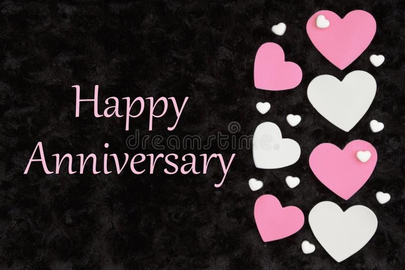 结婚纪念日快乐招呼与与糖果心脏的白色和桃红色心脏在黑色 库存例证