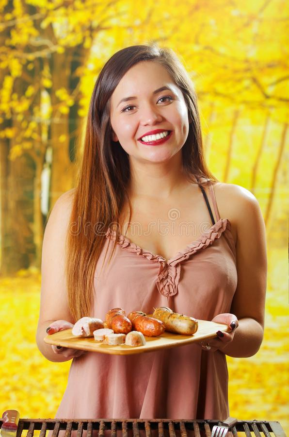 结束微笑的美丽的少妇停滞在她的手上在木切板,在的BBQ的烤香肠 库存图片