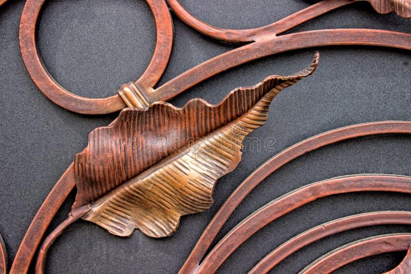结构和装饰锻铁门的细节 葡萄酒金属铜颜色图片 装饰纸卷和 免版税库存照片