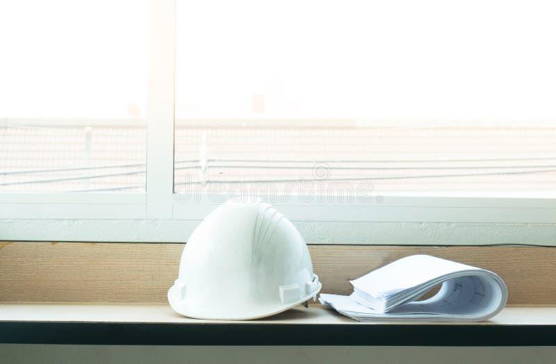 结构图图纸和白色安全帽在桌上 库存照片