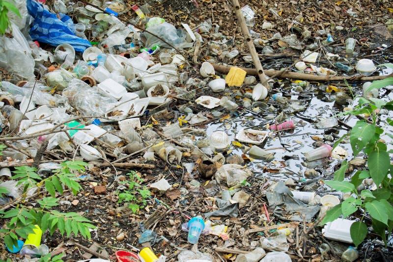 结果许多破烂物在河环境被毁坏 垃圾例如塑料,泡沫,瓶 肮脏的废物和难闻的气味 免版税库存图片