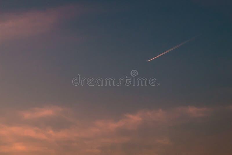 结露反向喷气机足迹可看见的踪影在从在大气发生后边的水蒸气或冰晶的天空中 库存图片