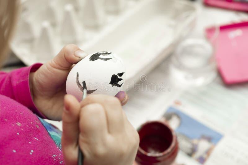 绘与刷子和水彩的孩子细节一个复活节彩蛋 库存照片