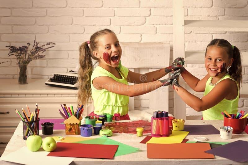绘与在桌上的树胶水彩画颜料油漆的女孩画家 免版税图库摄影