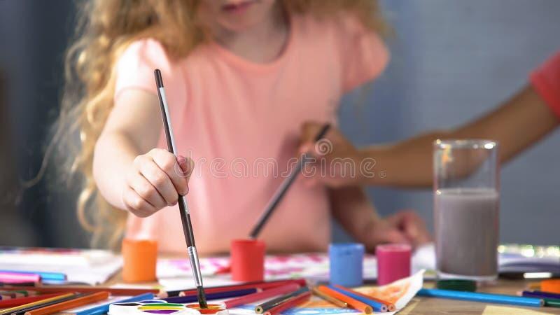 绘与树胶水彩画颜料的孩子在艺术教训在小学,童年 库存图片