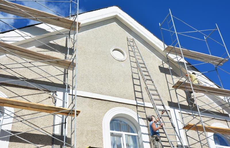 绘和涂灰泥外部议院脚手架墙壁 家庭门面绝缘材料、sctucco和绘画工作在外墙期间 免版税图库摄影