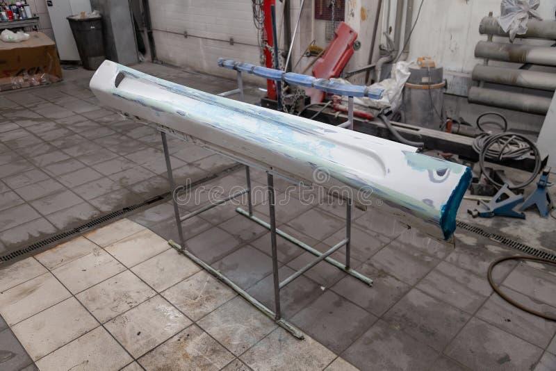 绘和烘干在专业箱子车身零件在应用油灰和油漆以后在侧梯在身体维修车间 库存图片