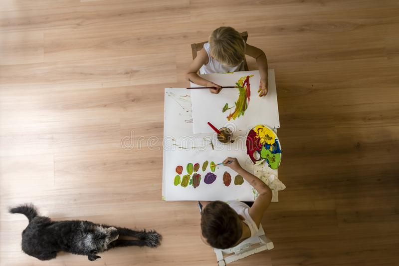 绘在与说谎在地板上的狗的桌上的孩子 免版税图库摄影