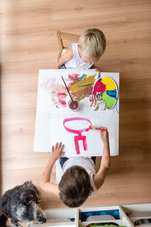 绘在小白色桌上的大角度观点的两个孩子 免版税库存图片