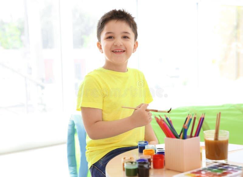 绘在桌上的逗人喜爱的小孩 库存图片