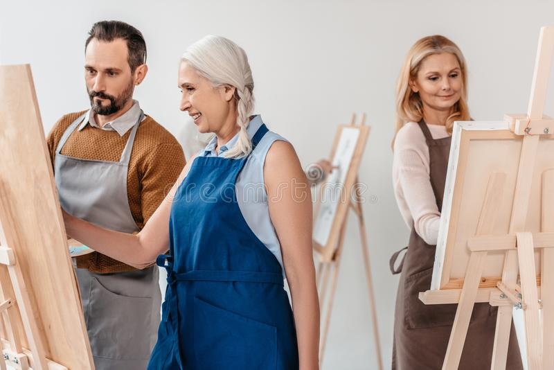 绘在画架的围裙的成熟学生在艺术课期间 免版税库存图片