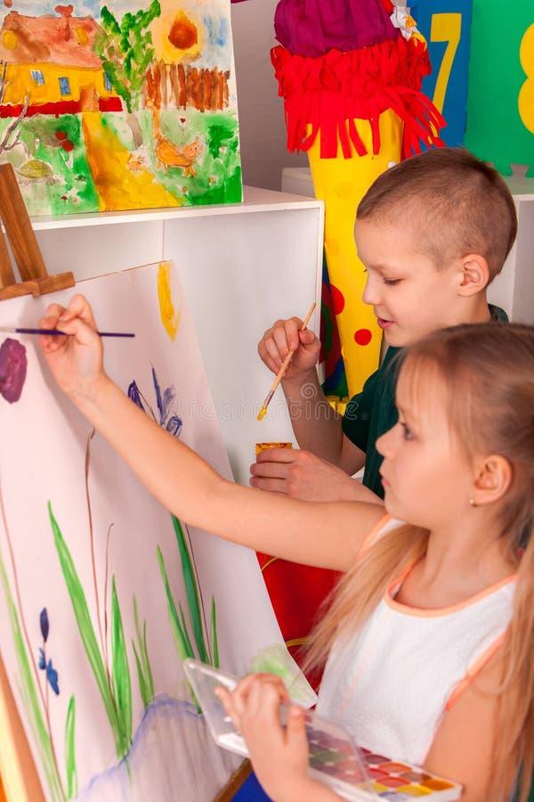 绘在画架的孩子手指 小组与老师的孩子 免版税图库摄影