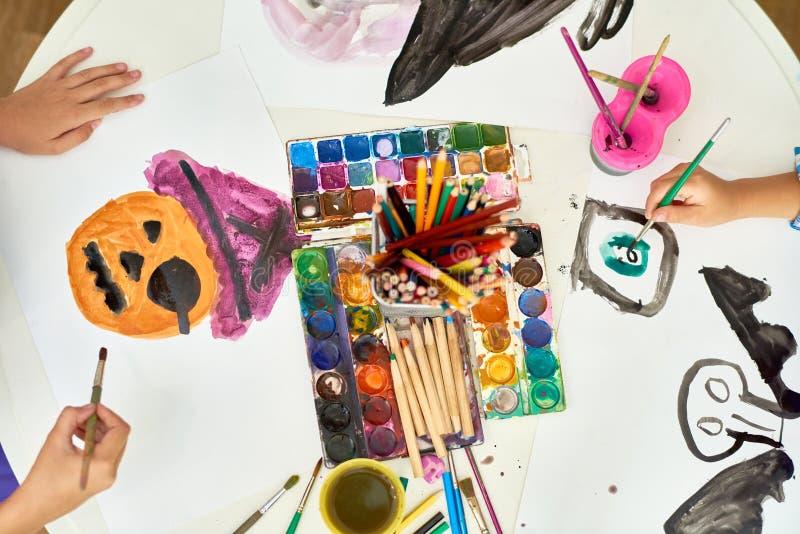 绘在艺术课的孩子万圣夜画 免版税库存图片
