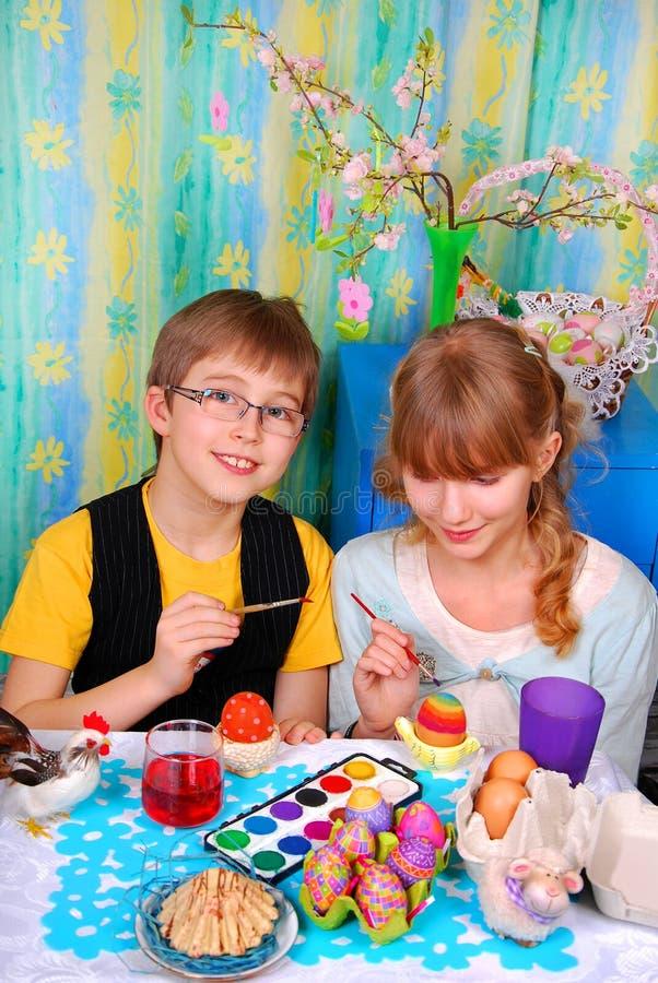 绘复活节彩蛋的女孩和男孩 图库摄影