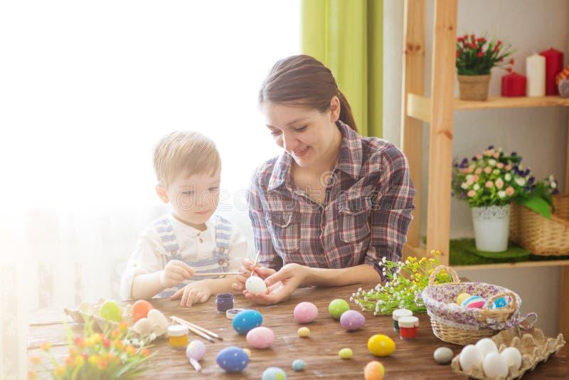 绘复活节彩蛋的母亲和儿子 幸福家庭妈妈和儿童儿子油漆与颜色的复活节彩蛋 准备的假日 库存照片