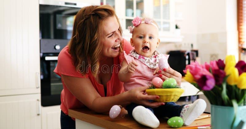 绘复活节彩蛋的母亲和她的婴孩 免版税库存照片
