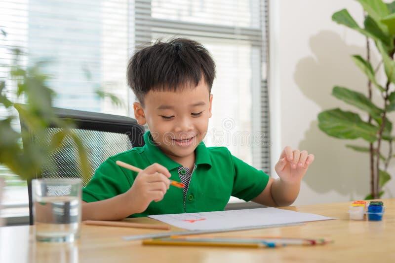 绘小男孩和桌的手创造性的 免版税库存图片