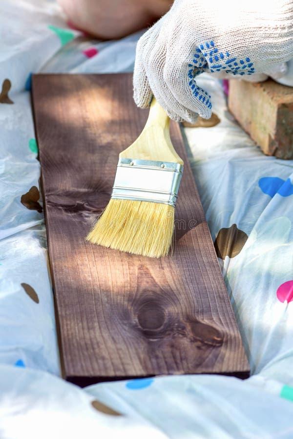 绘有一把宽刷子的一个木板一只手套的手的片段 免版税库存照片
