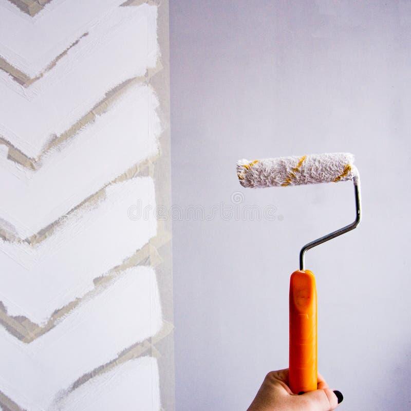 绘有修稿带的墙壁 在灰色墙壁上的白色之字形小条 拿着有油漆的手路辗 免版税库存照片
