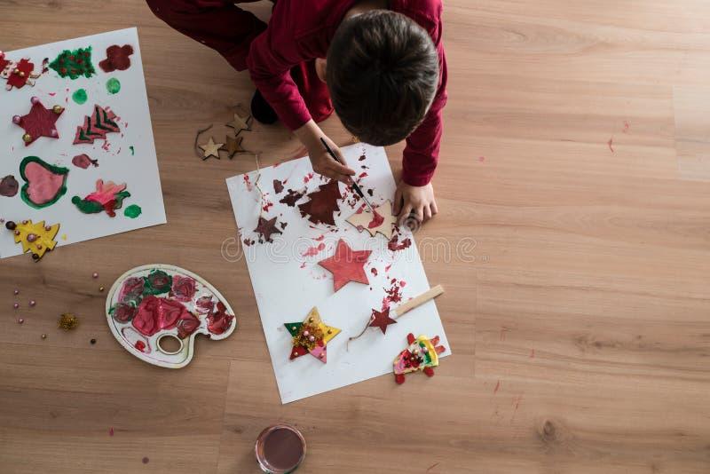 绘木圣诞节工艺品的男孩 免版税库存图片