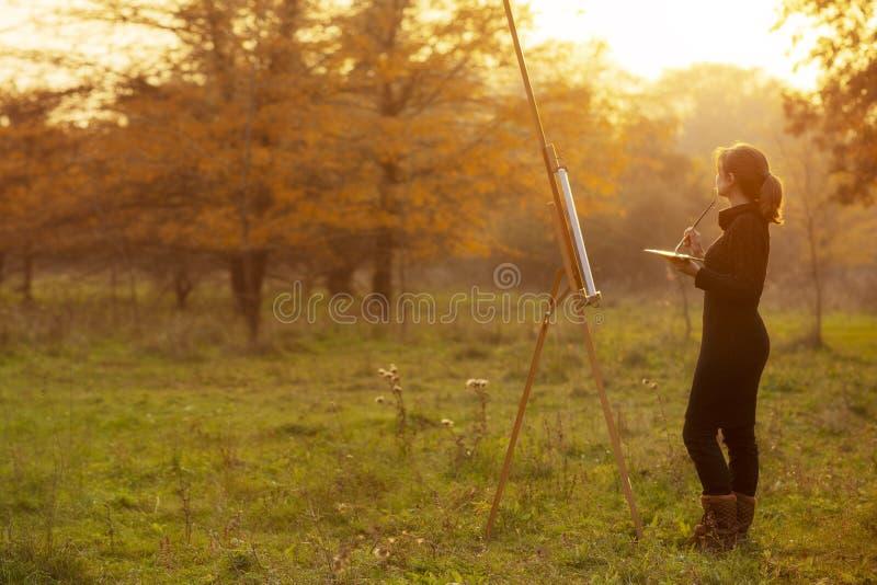 绘画的年轻女人艺术家图在画架,享受秋天自然和工作的女孩启发由美丽 库存照片