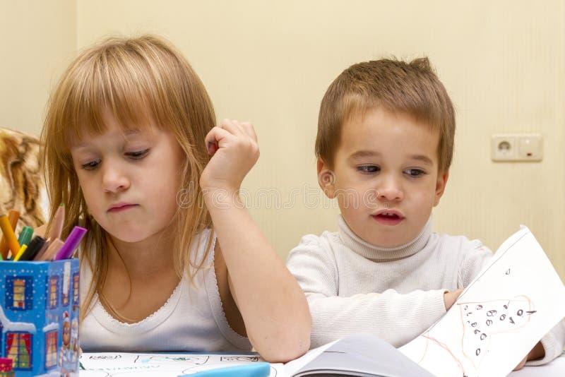 绘画的逗人喜爱的孩子在桌上户内 免版税库存照片