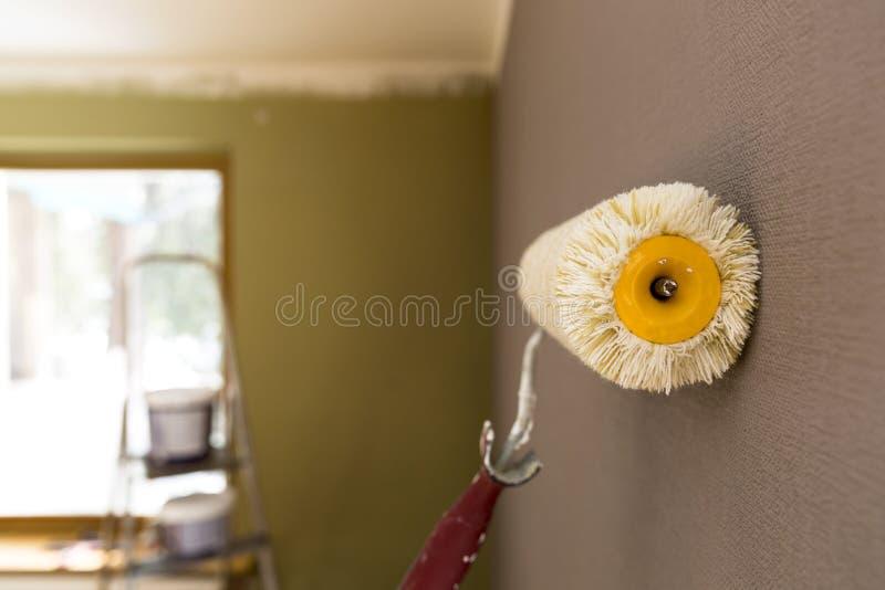 绘的路辗对灰色墙壁 在背景的梯子和油漆桶 图库摄影