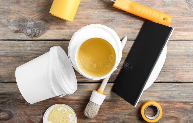 绘罐头和工具在木桌上 免版税库存图片