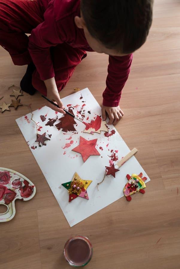 绘自创圣诞节装饰的年轻男孩 免版税图库摄影