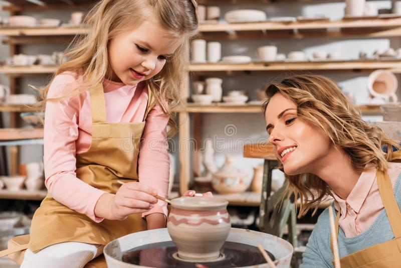 绘陶瓷罐的母亲和女儿 免版税库存图片