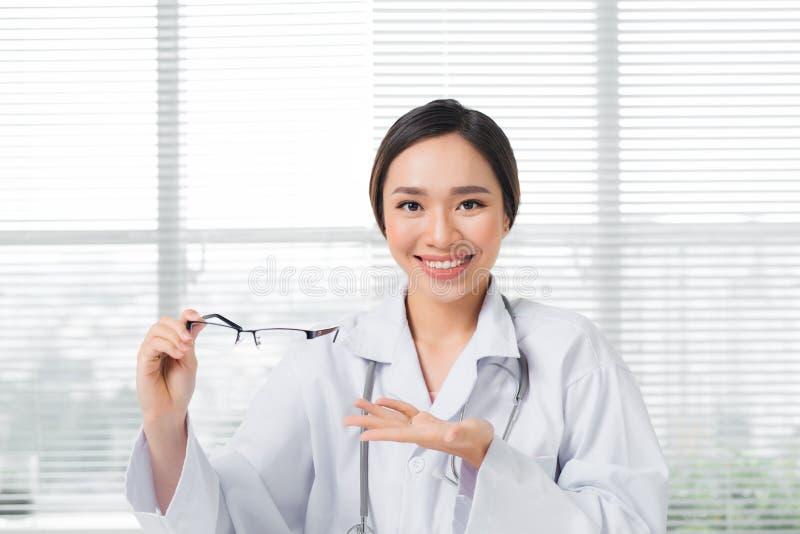 给一个对镜片的女性眼医 免版税库存照片