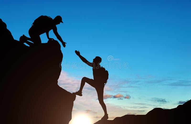 给一个帮手的一名男性登山家的剪影他的伙伴 库存例证