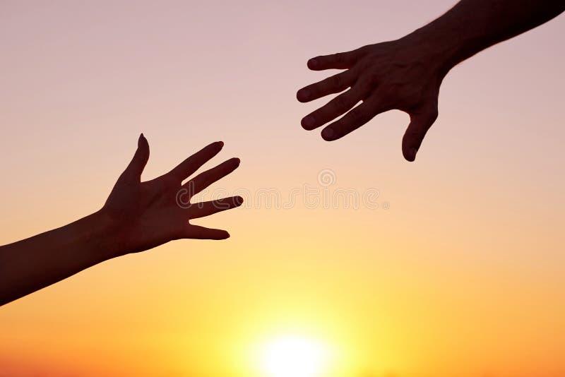 给一个帮手 现出轮廓两只手,男人和妇女,到达往彼此在天空日落 图库摄影