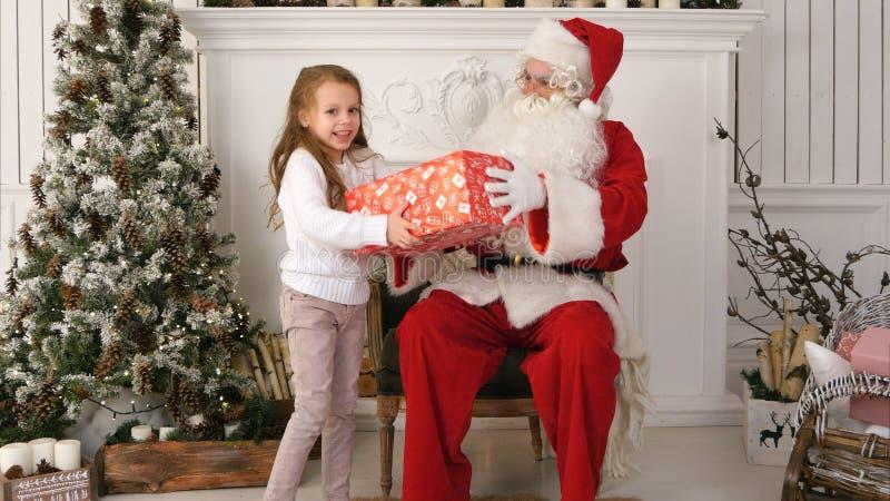 给一个恰好被包裹的礼物的圣诞老人一个逗人喜爱的小女孩 免版税图库摄影
