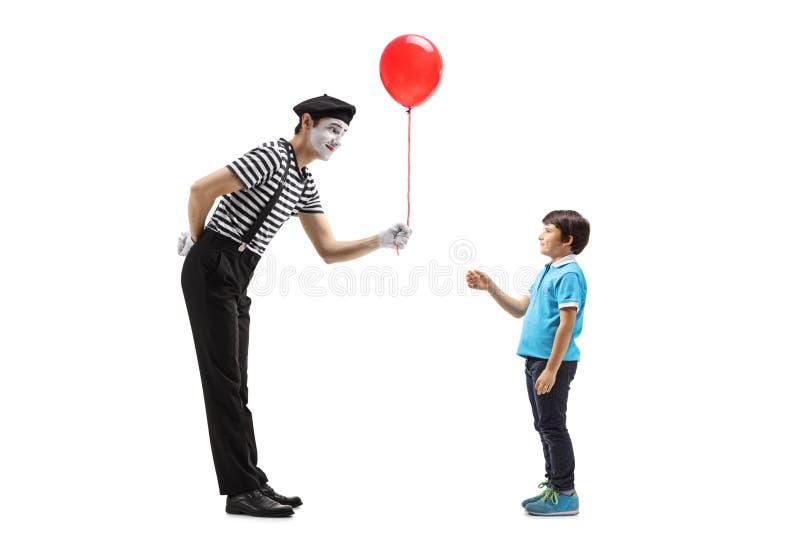 给一个红色气球的笑剧一个小男孩 库存图片