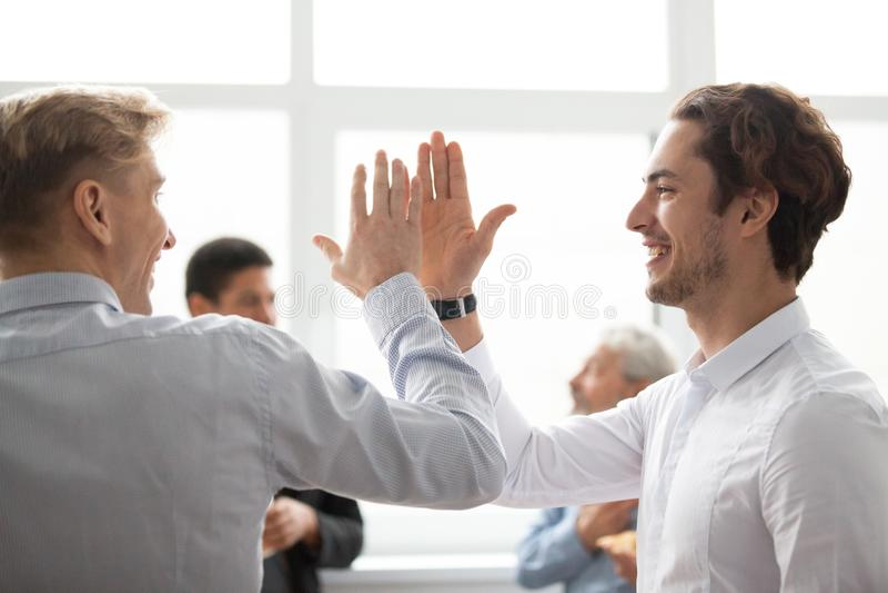 给上流五的微笑的男性同事在庆祝v的办公室 库存图片