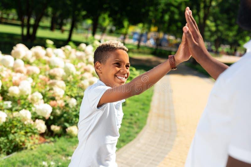 给上流五的快乐的正面年轻男孩 免版税图库摄影
