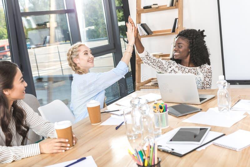 给上流五的愉快的多文化女实业家侧视图在工作场所 免版税库存图片