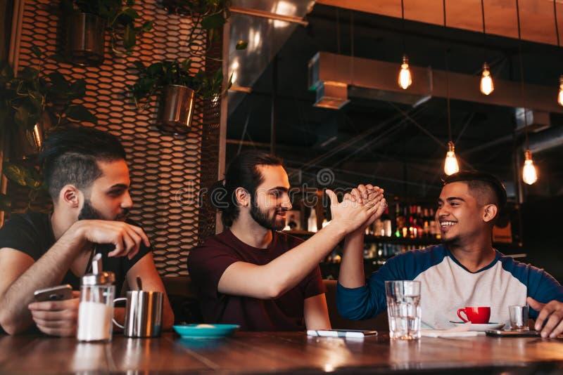 给上流五的愉快的阿拉伯年轻人他的朋友 小组混合的族种人获得乐趣在休息室酒吧 库存照片