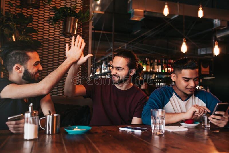 给上流五的愉快的阿拉伯年轻人他的朋友 小组混合的族种人获得乐趣在休息室酒吧 免版税库存图片