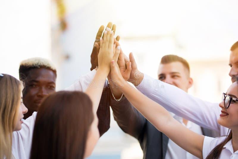 给上流fives姿态的愉快的成功的多种族企业队,他们笑并且欢呼他们的成功 免版税库存照片