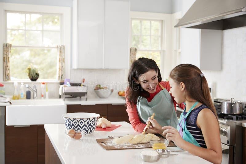 给与她的妈咪的犹太女孩被打褶的鸡蛋面包面团上釉 库存图片