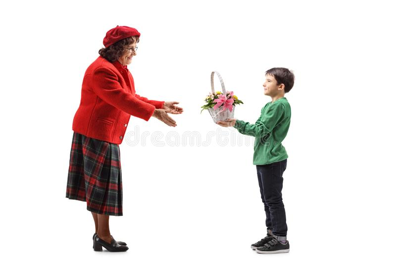 给与花的年轻男孩一个篮子他的祖母 库存图片