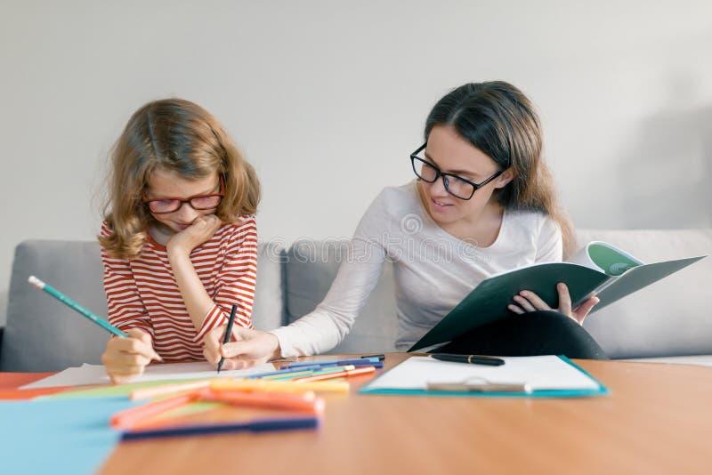 给专人上课的年轻女老师孩子,坐在她的在笔记本的书桌文字的女孩 免版税库存照片