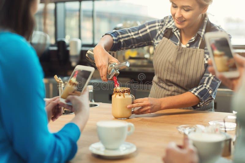 给主要类的老练的微笑的barista在咖啡店内部 库存图片
