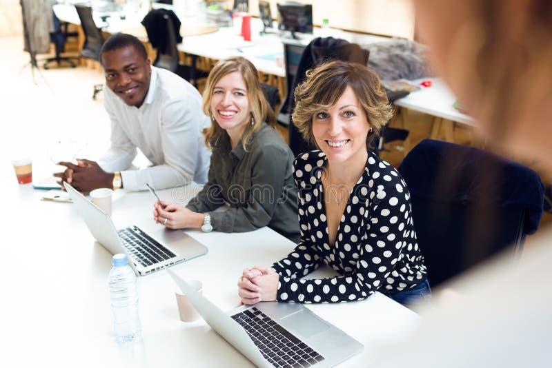 给予在会议的微笑的年轻买卖人注意关于coworking的地方 库存照片