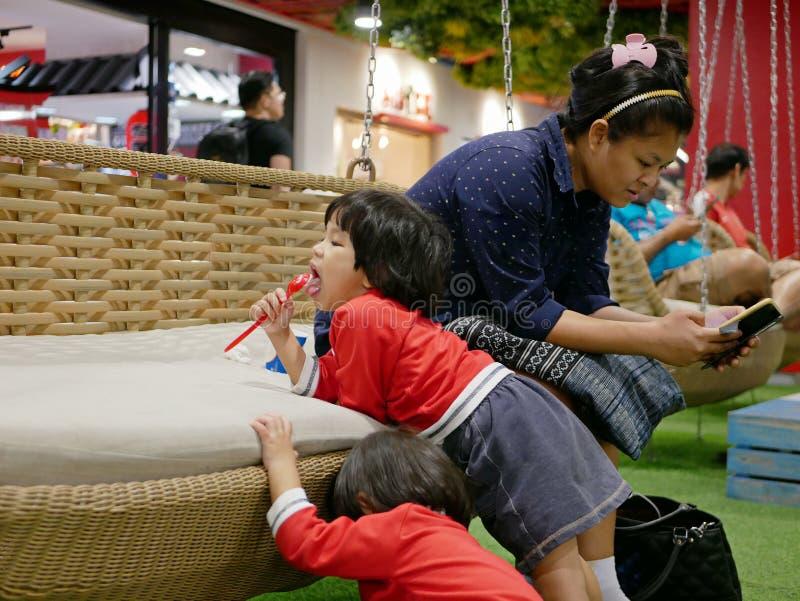 给予她的在智能手机的亚裔母亲单一关注忽略戏耍她的两个的婴孩 免版税库存照片